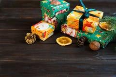 Presentes en Libro Verde anaranjado y en el fondo de madera para los amigos y la familia el hacer compras, Año Nuevo y concepto d imagenes de archivo