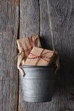 Presentes en una ejecución del cubo en una pared de madera rústica Fotos de archivo libres de regalías