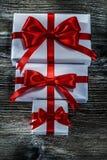 Presentes encajonados con los nudos rojos en el tablero de madera foto de archivo libre de regalías
