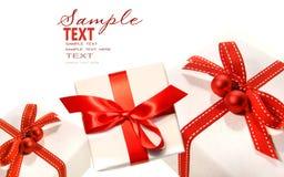 Presentes envolvidos com as fitas vermelhas isoladas no branco Imagens de Stock