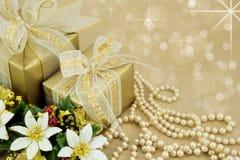 Presentes envueltos oro con las perlas y las flores Fotos de archivo