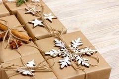 Presentes feitos a mão do Natal do ofício ou presentes rústicos dos presentes do ano novo no fundo de madeira Imagem de Stock Royalty Free