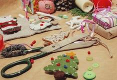 Presentes feitos a mão do Natal na confusão com brinquedos, velas, abeto, vintage de madeira da fita Imagem de Stock Royalty Free