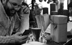 Presentes monocromáticos do Natal da escrita do homem da barba em uma tabela Foto de Stock
