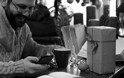 Presentes monocromáticos do Natal da escrita do homem da barba em uma tabela Fotos de Stock
