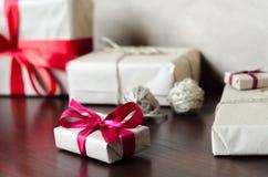 Presentes no papel de embalagem com fitas vermelhas Fotografia de Stock