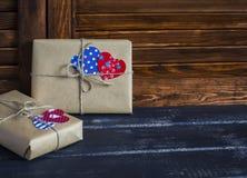 Presentes no papel de embalagem, corações de papel do dia de Valentim na superfície de madeira Fotografia de Stock Royalty Free