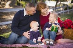 Presentes novos pequenos do Natal da abertura da família no parque Imagens de Stock