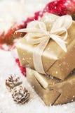 Presentes ou presentes de Natal com as decorações elegantes da curva e do Natal no fundo nevado brilhante Fotos de Stock Royalty Free