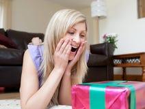 Presentes surpreendidos da abertura da mulher que encontram-se no assoalho Imagens de Stock Royalty Free