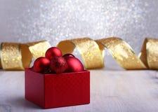 Presentes vermelhos coloridos com as bolas do Natal isoladas no fundo de prata fotografia de stock