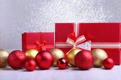 Presentes vermelhos coloridos com as bolas do Natal isoladas no fundo de prata fotografia de stock royalty free