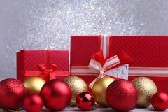 Presentes vermelhos coloridos com as bolas do Natal no fundo de prata fotografia de stock royalty free