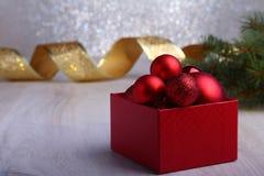 Presentes vermelhos coloridos com as bolas do Natal no fundo de prata imagem de stock