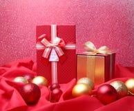 Presentes vermelhos coloridos com as bolas do Natal no fundo vermelho imagens de stock royalty free