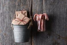 Presentes y bastones de caramelo que cuelgan contra una pared de madera rústica Imagen de archivo libre de regalías