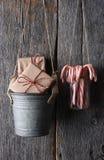 Presentes y bastones de caramelo que cuelgan en la pared rústica Imágenes de archivo libres de regalías