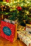 Presentes y caramelos de chocolate que esperan para ser abierto debajo del árbol de navidad Imagen de archivo libre de regalías