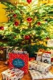 Presentes y caramelos de chocolate que esperan para ser abierto debajo del árbol de navidad Imágenes de archivo libres de regalías