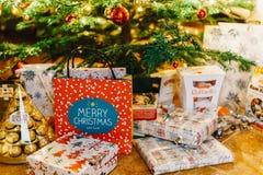Presentes y caramelos de chocolate que esperan para ser abierto debajo del árbol de navidad Foto de archivo