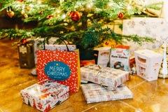 Presentes y caramelos de chocolate que esperan para ser abierto debajo del árbol de navidad Fotografía de archivo libre de regalías