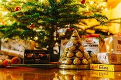 Presentes y caramelos de chocolate que esperan para ser abierto debajo del árbol de navidad Foto de archivo libre de regalías
