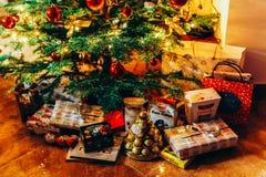 Presentes y caramelos de chocolate que esperan para ser abierto debajo del árbol de navidad Fotografía de archivo