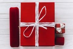Presentes y joyero elegantes del rojo en fondo de madera rústico Imágenes de archivo libres de regalías