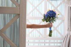 Presenti ad un mazzo la porta blu della mano dei fiori fotografia stock libera da diritti