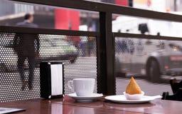 Presenti all'aperto con una tazza di caffè e un alimento di coxinha brasiliano immagine stock libera da diritti