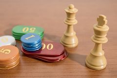 Presenti i giochi, gli scacchi ed i chip del casinò su una tavola di legno fotografia stock