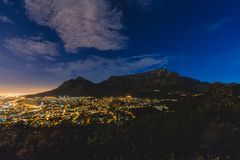Presenti la montagna e la ciotola della città di Cape Town alla notte con le nuvole fotografia stock