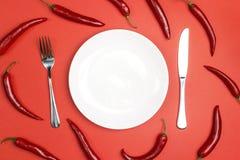 Presenti la regolazione con la coltelleria ed il peperoncino sulla tavola rossa copia fotografie stock