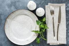 Presenti la regolazione con il tessuto vuoto del piatto, della coltelleria e della tavola immagine stock
