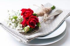 Presenti la regolazione con le rose rosse, i tovaglioli e le terrecotte dell'annata Fotografie Stock