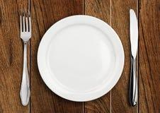 Presenti la regolazione, il piatto vuoto e l'argenteria sulla tavola di legno, v superiore Immagini Stock Libere da Diritti