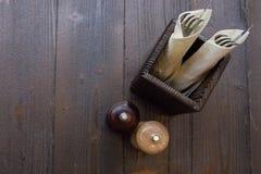 Presenti la regolazione sulla vista di legno scura del piano d'appoggio Gli agitatori di pepe e di sale con la coltelleria hanno  Immagini Stock