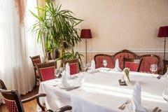 Presenti la regolazione in un ristorante, caffè nello stile dell'Unione Sovietica Tovaglia bianca, vetri, apparecchi, mobilia ros fotografie stock