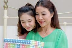 Presenti per la mamma, la madre felice e giovane la tenuta della figlia presenti per fotografie stock