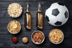 Presenti in pieno degli spuntini e della birra per calcio di sorveglianza sulla TV, vista superiore immagini stock libere da diritti