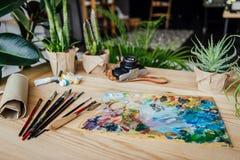 Presenti in pieno delle piante verdi conservate in vaso, dei rifornimenti di arte e della macchina fotografica d'annata immagine stock