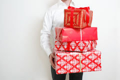 Presenting alot of gifts. A man presenting several christmas presents Royalty Free Stock Photography