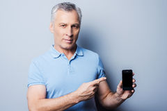 Presenting brand new smartphone. Royalty Free Stock Image