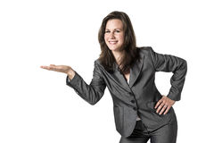 Presenting business woman. Aughing business woman presenting something in a gray suit isolated on white background Stock Photo