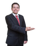 Presenting businessman in a black suit Royalty Free Stock Photo