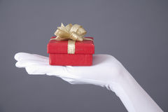 Presenting Christmas gift. Woman's hand with gloves holding a gift box against red background Stock Image