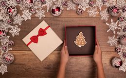 Presenting a christmas gift box - with gingerbread cookie inside Stock Photos