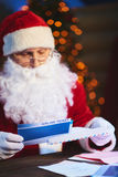Presenting Christmas journey. Santa Claus putting airline tickets into envelope Stock Photography