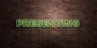 PRESENTING - fluorescent Neon tube Sign on brickwork - Front view - 3D rendered royalty free stock picture Stock Photography