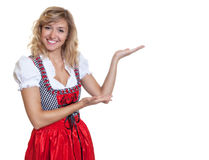 Presenting german woman in a traditional bavarian dirndl. On an isolated white background for cut out royalty free stock photo
